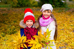 Two little girls in autumn park with leafs Stock Images
