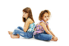 Two little girls back to back in quarrel. Isolated on white background Stock Photo