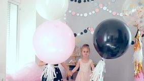 Two little girls with balloons on holiday. Jump and laugh stock video
