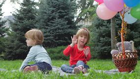 Two little girls with balloons in the park. Family having picnic in summer park. Feet Barefoot on Green Grass. Healthy Lifestyle. Spring Time stock video