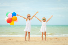 Two little girls with balloons standing on the beach at the day Royalty Free Stock Photo