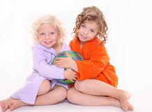 Two little girls in bathrobe. Two kids sitting in the floor, holding baloon Royalty Free Stock Photo