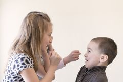 Two little girls beat the boy. Light background. European appearance. stock image