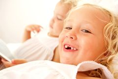 Two little girls on bed at home. Close up portrait of smiling adorable girl on bed with sister using digital tablet in background stock photo