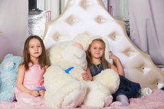 Two little girls in bed with toys Royalty Free Stock Photos