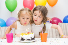 Two little girls at a birthday party Stock Photos