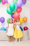 Two little girls at a birthday party Stock Images