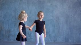 Two little girls in black ballet bathing suits have a good time on a gray background in studio of the ballet. Two lovely. Two little schoolgirls of ballet school stock video
