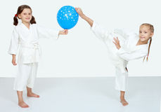 Two little girls with blue ball beat a karate kick leg. Two girls with blue ball beat karate kick royalty free stock image