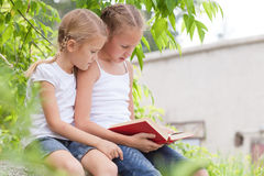 Two little girls with book sitting in the park Royalty Free Stock Image