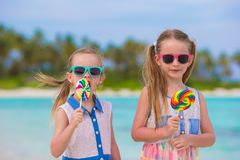 Two little girls with bright tasty lollipops on Royalty Free Stock Photos