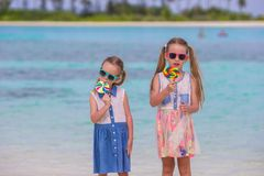 Two little girls with bright tasty lollipops on Royalty Free Stock Images