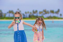 Two little girls with bright tasty lollipops on Stock Image