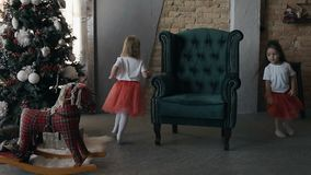 Two little girls - brunette and blonde run around a soft armchair near a Christmas tree on Christmas Eve. Slow motion stock video footage