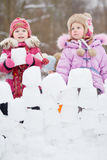 Two little girls build wall from snow blocks Stock Photos