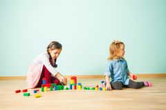 Two little girls building with blocks at home. Two little adorable girls building with blocks sitting on a wooden floor at home. Girls creating toy city of stock image