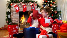 Two little girls in caps of Santa Claus sitting on the floor wit. H gifts in the room with the Christmas tree stock footage