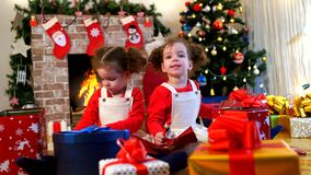 Two little girls in caps of Santa Claus sitting on the floor wit. H gifts in the room with the Christmas tree stock video