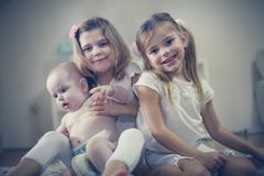 Two little girls care a baby brother. Two sisters and little brother stock photos