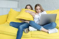 Two little girls in casual clothes sitting together on yellow sofa at home stock photo