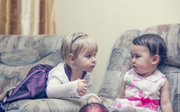 Two little girls chattingl on a sofa Stock Images