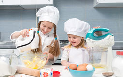 Two little girls in chef uniform with ingredients on table Royalty Free Stock Photography