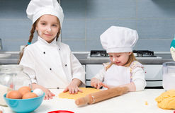 Two little girls in chef uniform with ingredients on table Stock Photos