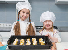 Two little girls in chef uniform with ingredients on table Royalty Free Stock Image