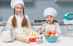 Two little girls in chef uniform with ingredients on table Royalty Free Stock Photos