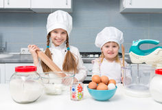 Two little girls in chef uniform with ingredients on table Stock Photography