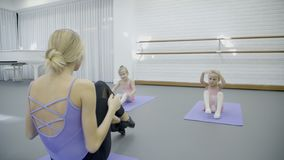 Two little girls at class in ballet school. Adorable children sit on gymnastic mat and knock their feet on floor with hands up, copying movements of female stock footage