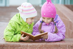 Two little girls in coats reads book Royalty Free Stock Images