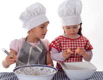 Two little girls in the cook costume. At the kitchen preparing the cake stock photography