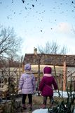 Two little girls in the countryside watching a flock of birds Royalty Free Stock Photo