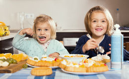 Two little girls with cream desserts. Happy smiling cute little girls with cream desserts at home kitchen Stock Photography