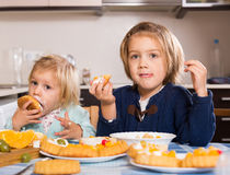 Two little girls with cream desserts royalty free stock photos