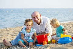 Two little girls with dad at sea Stock Photography