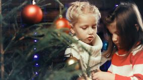 Two little girls decorate a Christmas tree. Two little girls decorates the Christmas tree round balls stock footage