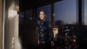 Two little girls decorate a window with the help of artificial snow. Preparing for the New Year and Christmas. Girl decorates a window with the help of stock footage