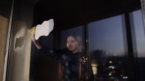 Two little girls decorate a window with the help of artificial snow. Preparing for the New Year and Christmas. Girl decorates a window with the help of stock video footage