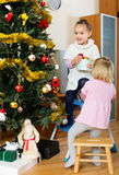 Two little girls decorating Christmas tree Stock Image
