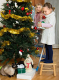 Two little girls decorating Christmas tree Stock Photos