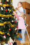 Two little girls decorating Christmas tree Royalty Free Stock Images