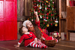 Two little girls decorating Christmas tree. New Stock Photos