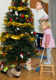 Two little girls decorating Christmas tree Royalty Free Stock Photos