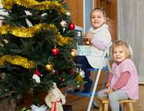 Two little girls decorating Christmas tree Royalty Free Stock Photo