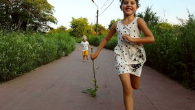 Two little girls in different cloths run to the camera.  stock video footage