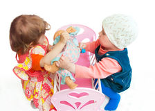 Two little girls divide a doll Royalty Free Stock Photography