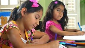 Two little girls doing homework smile at camera stock video