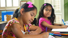 Two little girls doing homework smile at camera. Two little girls quietly doing homework in their workbooks look up and smile stock video footage